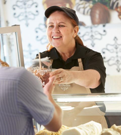 Kilwins employee handing a caramel apple to a customer.