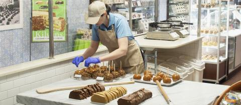 A Kilwins employee sprinkles toppings on freshly dipped caramel apples.
